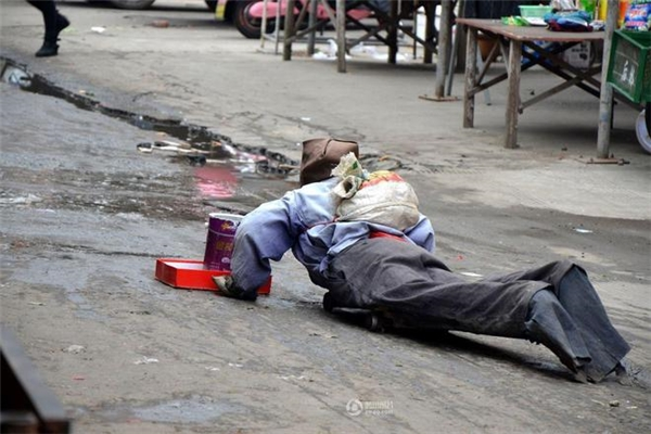 Một người đang ông tàn tật lết trên đường phố đi xin ăn...