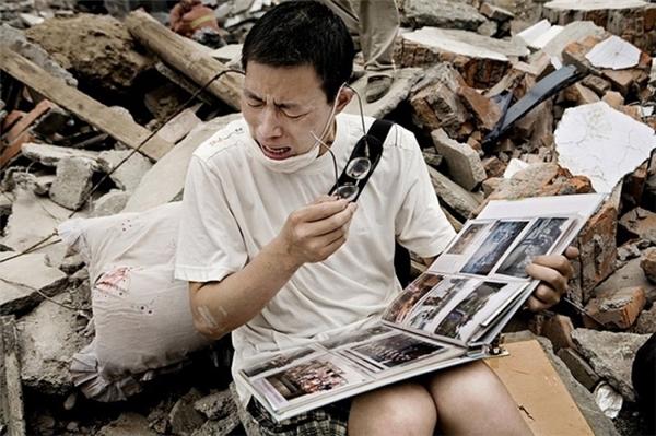 Người đàn ông không kiềm được nước mắt sau khi tìm thấy chiếc album ảnh của gia đình mình sau trận động đất khiến cho ngôi nhà hoàn toàn bị phá hủy.