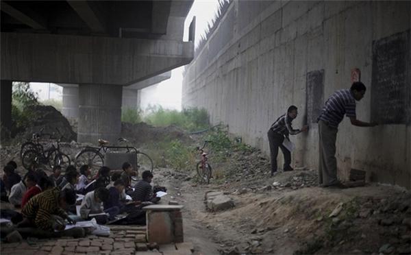 Hai giáo viên tốt bụng dạy chữ miễn phí cho trẻ em nghèo bên dưới một cây cầu vượt ở New Delhi, Ấn Độ.