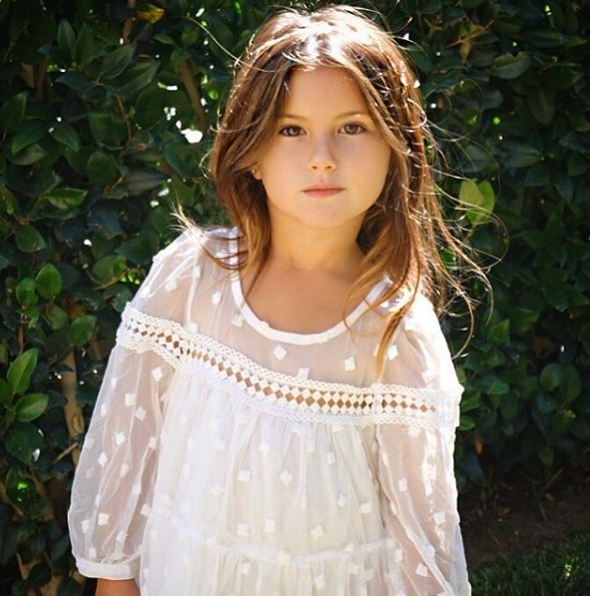 Cô bé có mái tóc vàng óng ánh và khuôn mặt xinh đẹp với những đường nét thanh mảnh.