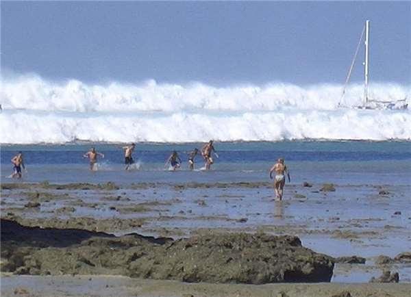 Mọi người bỏ chạy hoảng loạn khi thấy một cơn sóng đang bắt đầu dâng lên.