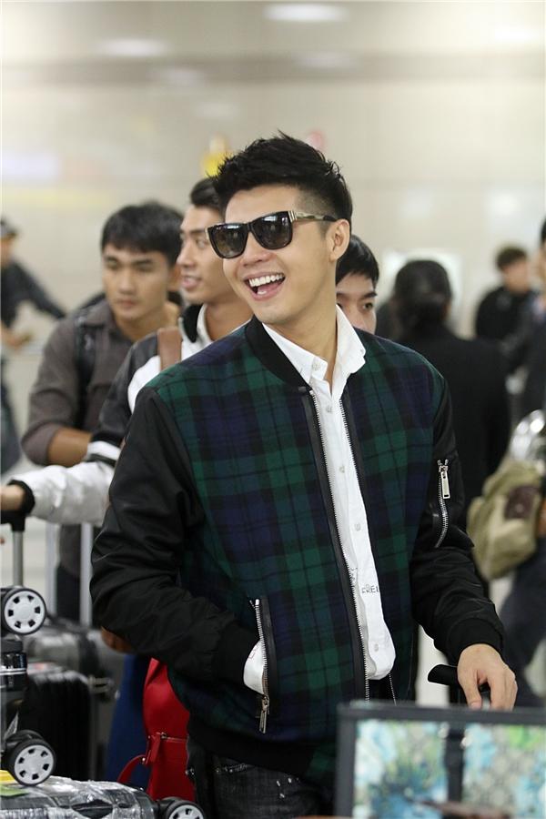 Trang phục sân bay của nam ca sĩ khá đơn giản với sơ mi trắng, quần jeans cùng bomber jacket caro hợp xu hướng.