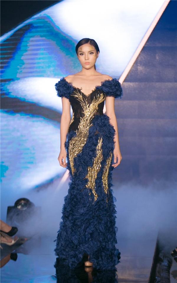 Kỳ Duyên diện bộ váy đuôi cá bó sát khoe đường cong gợi cảm. Thiết kế kết hợp những mảng chất liệu với 3 tông màu: đen, xanh, vàng làm chủ đạo.