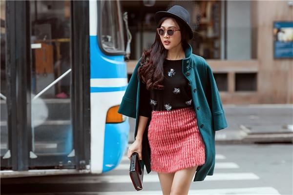 Cách phối trang phục nhiều lớp luôn được xem là nét đặc trưng trong mùa mốt cuối năm. Áo măng tô xanh cổ vịt kết hợp cùng tông hồng đào, sắc đen trầm mặc tạo nên bộ trang phục có chiều sâu về cảm quan thị giác.
