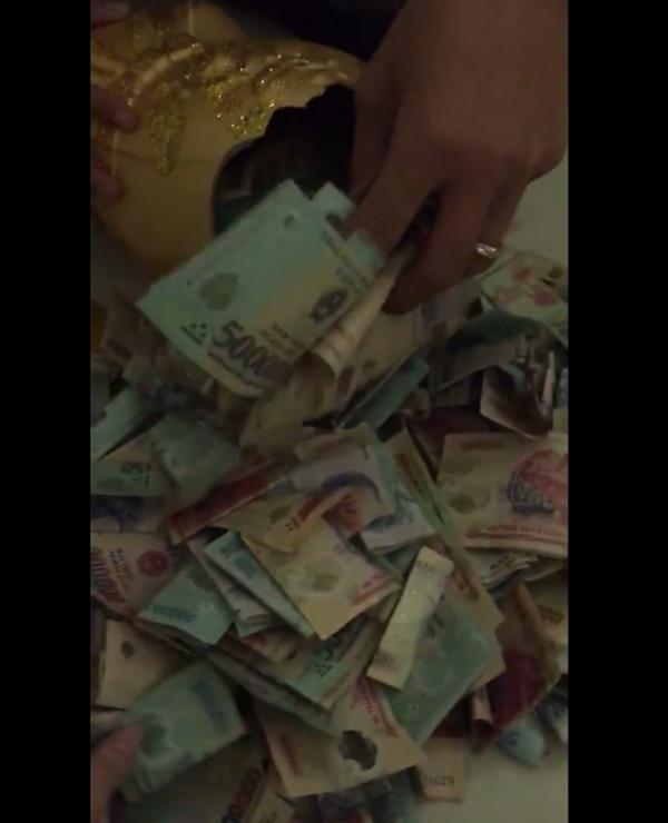 Số tiền đầy ắp bên trong conheo đất khiến dân mạng không ngớt xuýt xoa.(Ảnh: Cắt clip)