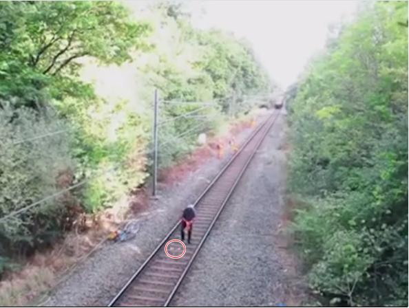 Người đàn ông say rượu cố nhặt đồ bị rơi dù biết đang có đoàn tàu tới gần.(Ảnh: Cắt clip)