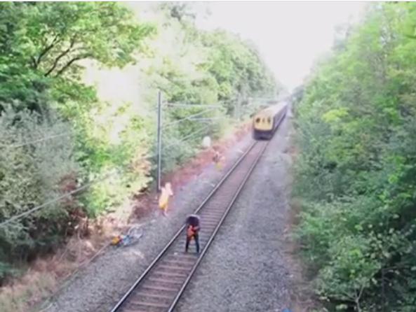 Các công nhân đường sắt gần đó chứng kiến và lao nhanh tới mong cứu người đàn ông này.(Ảnh: Cắt clip)