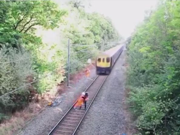 Một công nhân lao mình cứungười đàn ông say rượunhảy ra khỏi đường ray.(Ảnh: Cắt clip)