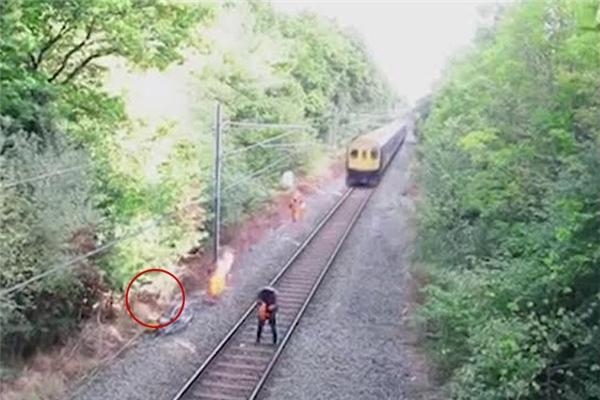 Chiếc bóng của người công nhân đường sắt in trên bụi cỏ ven đường.(Ảnh: Cắt clip)