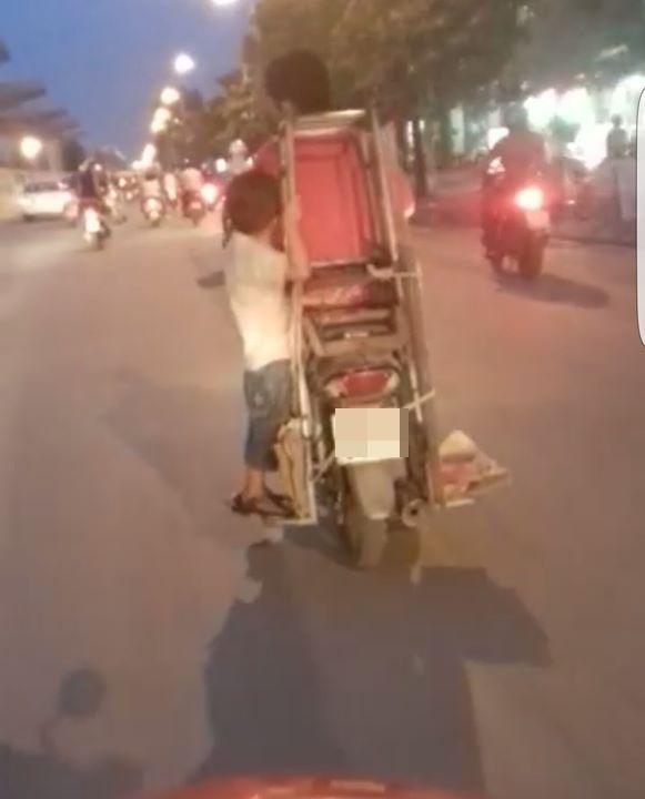 Có thể thấy rằng bé trai đang bám vàochiếc khung gỗ được buộc cố định ở yên xe.