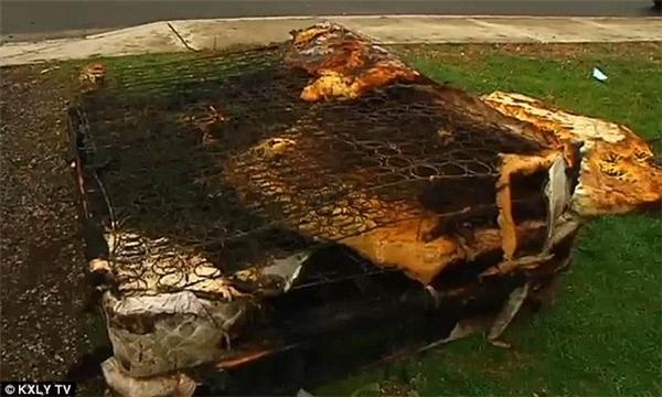 Một chiếc giường chỉ còn phần khung và than sau đám cháy.
