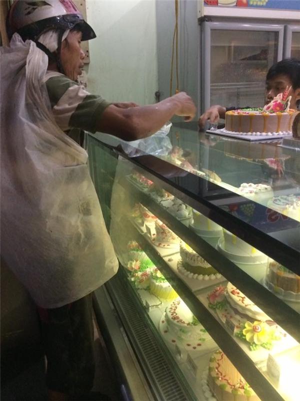 Hình ảnh người bố đang mua bánh kem cho con gái.