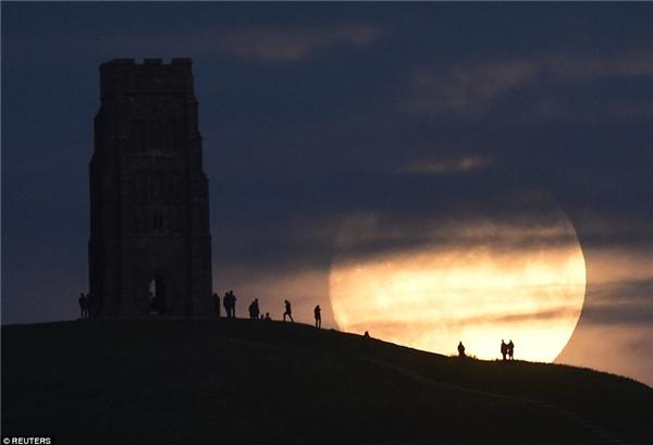 Người dân thị trấn Glastonbury quan sát mặt trăng dần mọc trong đêm 13/11. Để quan sát tốt nhất, người xem nên rời khỏi thành phố vì ánh đèn đô thị và các đám mây có thể làm lu mờ mặt trăng, khiến nó chỉ trông giống như trăng tròn bình thường. (Ảnh: Reuters)