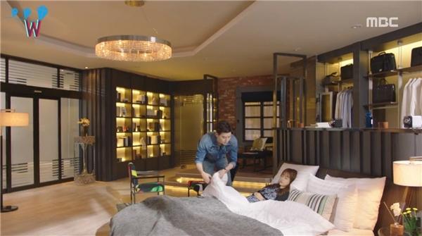 Phòng ngủ có không gian rộng nhưng mang lại cảm giác ấm cúng cho cách bố trí vật dụng hợp lí. Đằng sau chiếc giường chính là tủ quần áo, phía bên kia là chiếc kệ trưng bày những vật dụng khác được thắp sáng đèn vô cùng nổi bật vào ban đêm.
