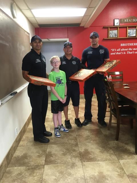 Ryan mang tặng bánh pizza cho những chú lính cứu hỏa.