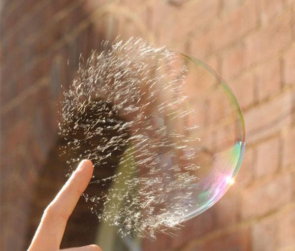 Ngón tay vừa chạm vào một bong bóng nước. Bong bóng chưa vỡ hết, phân nửa vẫn còn hình dạng.