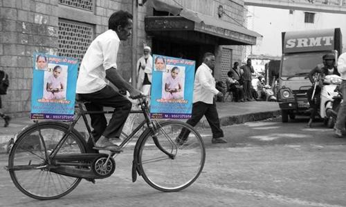Singh trên chiếc xe đạp cà tàng với 2 tấm poster hai bên xe có hình ảnh vợ mình.
