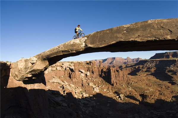 Khoảnh khắc ấn tượng của một người đi xe đạp trên cây cầu đá ở Canyonlands, Utah.
