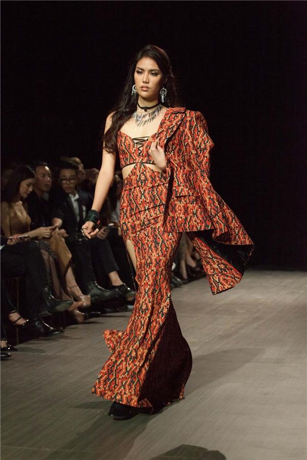 Mở màn bằng thiết kế với những đường cắt mạnh mẽ trên nền chất liệu in da trăn cách điệu cùng màu đỏ mê hoặc, siêu mẫu Lan Khuê ngay lập tức mang đến bầu không khí sôi nổi, đầy hào hứng cho sàn catwalk.