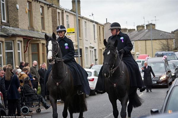 Đám tang được cảnh sát cưỡi ngựa hộ tống đến nghĩa trang.