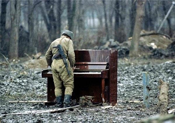 #2 Một người lính Nga dừng lại và chơi một bản cùng chiếc đàn piano bị vứt bỏ ở Chechnya năm 1994.(Ảnh: Life Buzz)