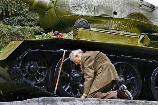 #6 Người cựu binh Nga trong Thế chiến II quỳ bên cạnh chiếc xe tăng từng gắn bó với ông qua biết bao khói lửa chiến trường, nay nằm khiêm tốn trong một bảo tàng tại một thị trấn nhỏ của Nga.(Ảnh: Life Buzz)