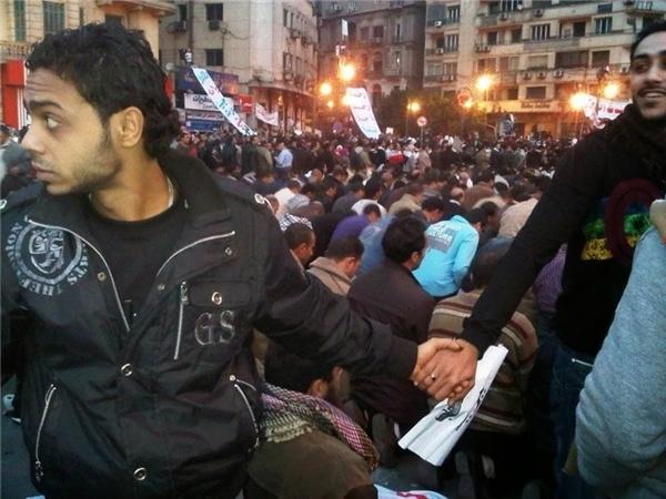 #7 Những người theo đạo Thiên Chúa chung tay bảo vệ những người Hồi giáo trong lúc cầu nguyện vào khoảng giữa năm 2011 trong cuộc nổi dậy ở Cairo, Ai Cập.(Ảnh: Life Buzz)