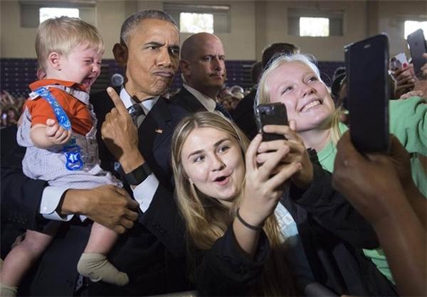 Gương mặt hài hước của tổng thống Obama khi bế một em bé và cùng selfie với người dân trong một sự kiện tranh cử của bà Hillary Clinton ngày 1/11.