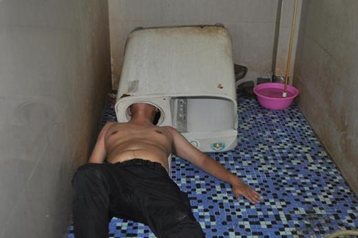 Sau này có sửa máy gì thì cũng đừng tự sửa nhé, nếu không sẽ giống trong người đàn ông trong bức ảnh này! Anh ta đang cố gắng chui đầu vào sửa máy, ai ngờ...kẹt luôn không thoát ra được. Hình ảnh chụp tại Trung Quốc ngày 29/05/2016.