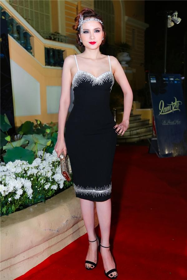 Hoa hậu Diễm Hương kết hợp dáng váy hai dây đơn giản cùng dây thắt lạ mắt ở đầu. Thiết kế được nhấn nhá bằng chi tiết ánh bạc trên nền đen tựa như bầu trời đêm với những vì sao lấp lánh.