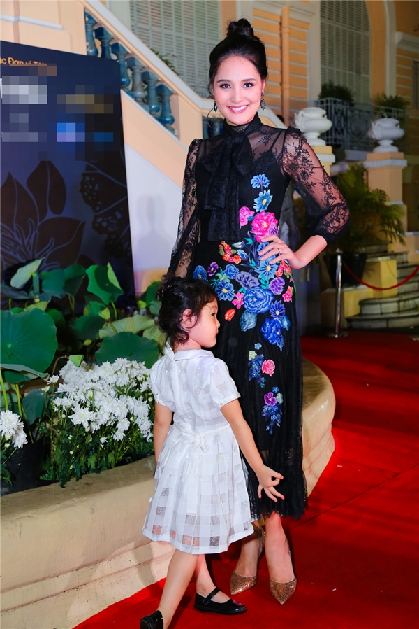 Hoa hậu Hương Giang dẫn theo con gái thưởng thức đêm tiệc thời trang này. Bộ váy đen của cô trở nên nổi bật nhờ hoạ tiết hoa tông màu hồng, tím ngọt ngào, đan xen một cách tinh tế.