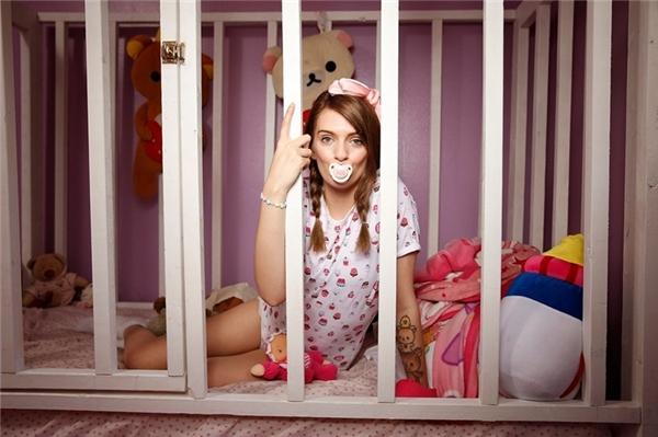 """Bức ảnh chụp cô gái từng bị lạm dụng có tên Jess (21 tuổi) ngồi trong chiếc giường đặc biệt của mình tại nhà riêng ở Florida, Mỹ. 9X được gọi là """"em bé người lớn"""" bởi cô thích mặc tã lót, ngậm núm vú giả... giống hệt một đứa trẻ sơ sinh."""