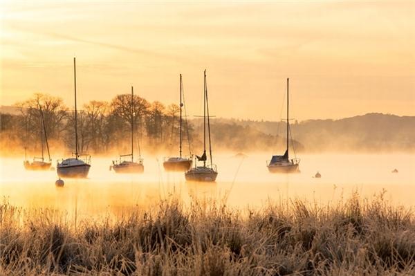 Khoảnh khắc đẹp như tranh vẽ khi những chiếc thuyền buồm ẩn hiện trên mặt hồ Windermere (Anh) lúc bình minh ngày 5/12.