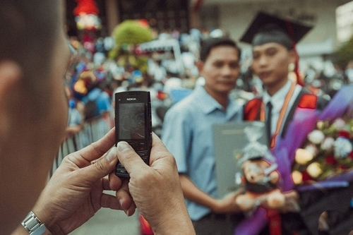 Trong ngày tốt nghiệp của con trai, người cha đã đến và dành cho con cái ôm đầy tình cảm. Điều đặc biệt khiến bức ảnh trở nên đặc biệt chính là ông dùng chiếc điện thoại cũ để lưu lại khoảnh khắc này.