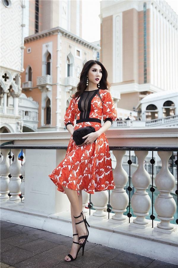 Chiếc váy xòe bồng bềnh nổi bật giữa đường phố xứ sở cờ hoa nhờ họa tiết tông đỏ nổi bật. Chất liệu xuyên thấu điểm xuyến trước ngực giúp nữ người mẫu khoe trọn lợi thế về vòng một gợi cảm. Nhờ phần vải lưới tông tối, bộ trang phục vẫn giữ được nét yêu kiều, quyến rũ vừa phải.