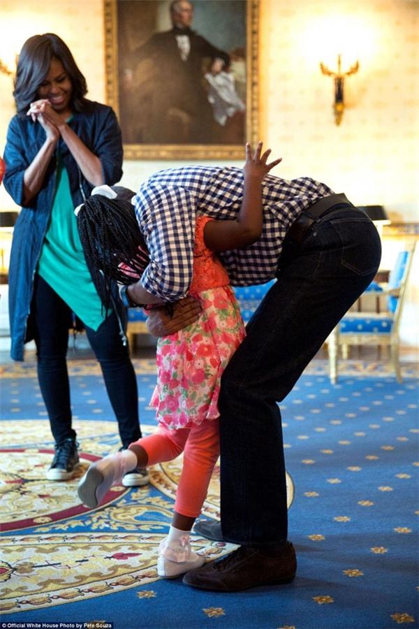 Ông Obama cúi người ôm chầm Caprina Harris – bé gái từng nổi tiếng với đoạn video bật khóc lúc nghe tin vị Tổng thống da màu sẽ hết nhiệm kì.