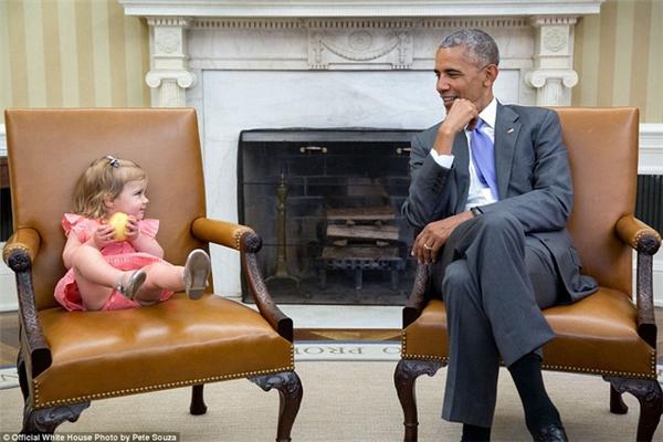 """Tổng thống Obama tay chống cằm, ngồi """"đấu mắt"""" với con gái của Cố vấn cấp cao David Axelrod tại Nhà Trắng."""