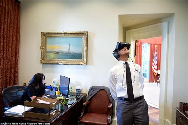 Tổng thống Obama hăng hái theo dõi phim thực tế ảo với thiết bị đặc biệt trong khi nhân viên của ông, cô Ferial Govashiri không hề quan tâm.