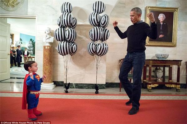 Tổng thống Obama giơ tay tạo dáng siêu nhân, chơi đùa cùng một bé trai trong dịp Halloween.