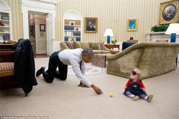 Ông Obama cởi áo khoác, quỳ hai chân xuống sàn, dùng một quả bóng để thu hút sự chú ý với bé gái concủa một quan chức chính phủ.