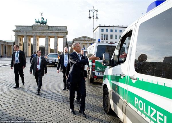 Thay vì đi ô tô, ông Obama tản bước trên đường về khách sạn ở Berlin, Đức hôm 17/11. Ông chìa tay hưởng ứng khi một người tài xế tỏ ý muốn bắt tay.