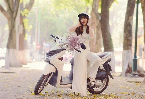 """Cô gái hồn nhiên trong tà áo dài giữa phố mùa thu Hà Nội - (Ảnh trong triển lãm """"Những sắc màu cuộc sống"""")."""