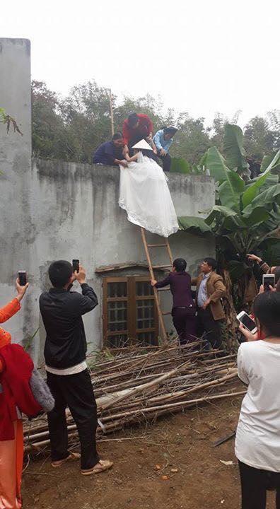 Cô dâu trong đang leo thang để vào được nhà chồng.