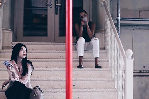 Tại một góc phố nhỏ ở nước ngoài, có một cô gái nhỏ xinh xắn ngồi bên cầu thang, đưa ánh nhìn về nơi xa xăm