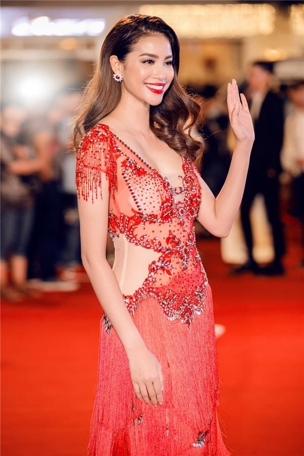 Trong tuần qua, Phạm Hương tiếp tục góp mặt trong danh sách mặc đẹp với thiết kế màu đỏ rực rỡ kết hợp vải xuyên thấu và chi tiết tua rua đính kết kì công của Đỗ Long. Bộ váy với phom ôm sát tôn dáng triệt để, làm nổi bật thân hình đồng hồ cát của cô.