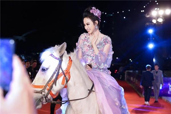 Angela Phương Trinh như nữ thần mùa xuân với thiết kế đính hoa màu hồng tím ngọt ngào của một thương hiệu danh tiếng có giá 200 triệu đồng. Phương Trinh chọn tông trang điểm ngọt ngào, tự nhiên hòa hợp với trang phục. Trong lần xuất hiện này, nữ diễn viên gây chú ý khi cưỡi ngựa lên thảm đỏ.