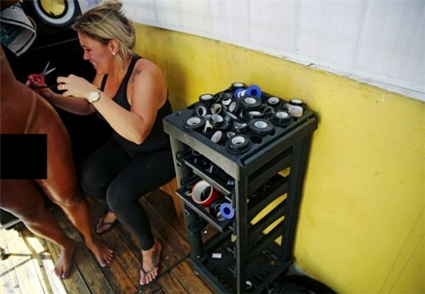 Erika Bronze, 34 tuổi, là chủ tiệm spa độc đáo này đang giúp khách hàng của cô diện một chiếc quần bikini bằng băng dính. (Ảnh:Reuters)