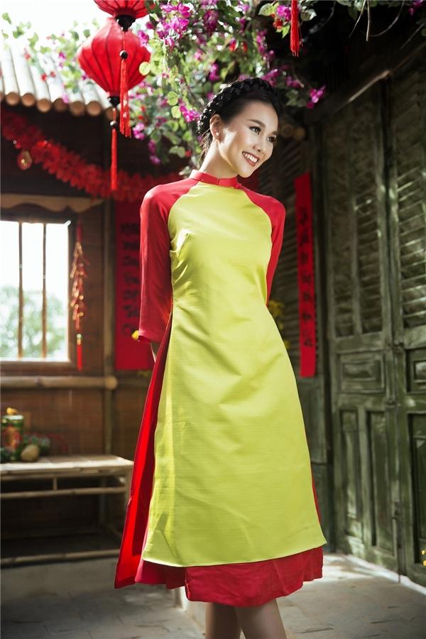 Bộ áo dài mang đậm hương vị ngày Tết với hai sắc màu chủ đạo đỏ và vàng. Bộ cánh được cách tân dài không quá đầu gối và xòe rộng tạo cảm giác năng động nhưng không kém phần nữ tính đặc trưng của người phụ nữ Á Đông.