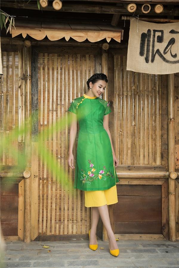 Bộ áo dài với thiết kế tay ngắn cùng gam màu xanh lá, vàng làm chủ đạo là bí kíp giúp các bạn nữ nổi bật khi xuống phố dạo chơi ngày đầu năm. Hai bên cầu vai được điểm xuyết tinh tế với họa tiết cành mai, đào mang không khí tươi vui của ngày Tết.