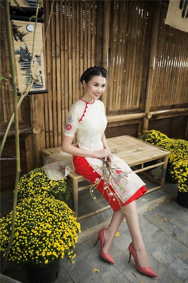 Thanh Hằng trở nên thanh lịch, dịu dàng trong tà áo dài màu trắng với họa tiết hoa rực rỡ thêu dọc theo thân tà áo.